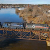 Pan Am freight PORU (Portland to Rumford) is seen crossing the old Maine Central Bridge across the Great Falls of the Androscoggin River. The train is crossing from Auburn into Lewiston, 12-3-20.