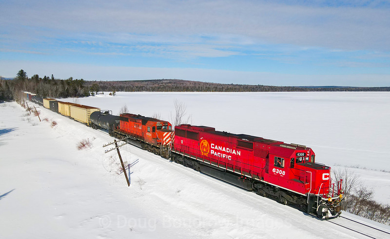 CP 250 is seen headed East along the Moosehead Sub shortly after departing Jackman, Maine. The train is passing along Long Pond and through the unincorporated area of the same name, 2-19-21.