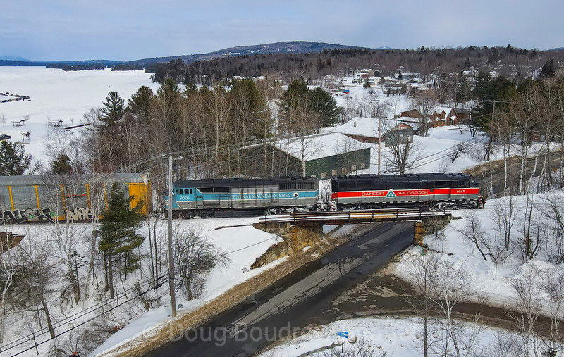 """Canadian Pacific 250 is seen coasting through Greenville, Maine along Moosehead Lake with Central Maine & Quebec power including the Bangor & Aroostook heritage unit. CP bought the Central Maine & Quebec last year but due to a power shortage, some of the CMQ """"barns"""" have been regularly seen on the Montreal to Brownville train. Ironically this line was originally Canadian Pacific before being sold 20 years ago. Likewise, the SD40-2F locomotives were built for the CP in 1988. They were purchased by the CMQ in 2015. Greenville is a popular place during Winter as it is nestled at the Southern edge of Moosehead Lake. Snowmobile riders and ice fisherman are frequent sights. In the background, snowmobile races are being held on the frozen lake, 2-20-21."""