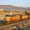 An Eastbound manifest freight is seen rolling down the hill into Reno at Verdi, Nevada near the state line just as the sun was coming up. The train which originated in Roseville, California has just passed over Donner Pass, 8-20-21.