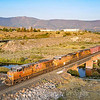 An Eastbound manifest freight is seen rolling down the hill into Reno over the Truckee River at Verdi, Nevada near the state line ,just as the sun was coming up. The train which originated in Roseville, California has just passed over Donner Pass, 8-20-21.