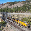 An Eastbound manifest train is seen crossing the Truckee River near Verdi, Nevada just after crossing the state line from California, 8-19-21.