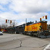 New England Southern is seen headed North with 8 loads, an unusually long train for them. Six of the cars are spine cars loaded with ties destined to be interchanged with Plymouth & Lincoln for a tie replacement project. The train is seen passing the old Boston & Maine depot in Northfield as the crew flags the busy unprotected crossing. The bridge is the town line and the head end is now in the town of Tilton, 4-22-20.