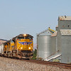 An Eastbound Union Pacific grain train is seen passing the grain silos in Rufus along the Columbia River Gorge. A flock of birds can be seen above the lead unit, 7-14-21.