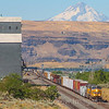 An Eastbound Union Pacific manifest freight train is seen passing through Biggs Junction and an abandoned grain elevator. The 11,250-foot peak of Mount Hood can be seen looming in the background, 7-15-21.