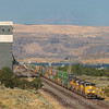 An Eastbound Union Pacific Z train is seen passing through Biggs Junction along the Columbia River Gorge. Mount Hood can be seen in the distance obscured by smoke from the numerous wildfires ongoing in the Pacific Northwest, 7-14-21.