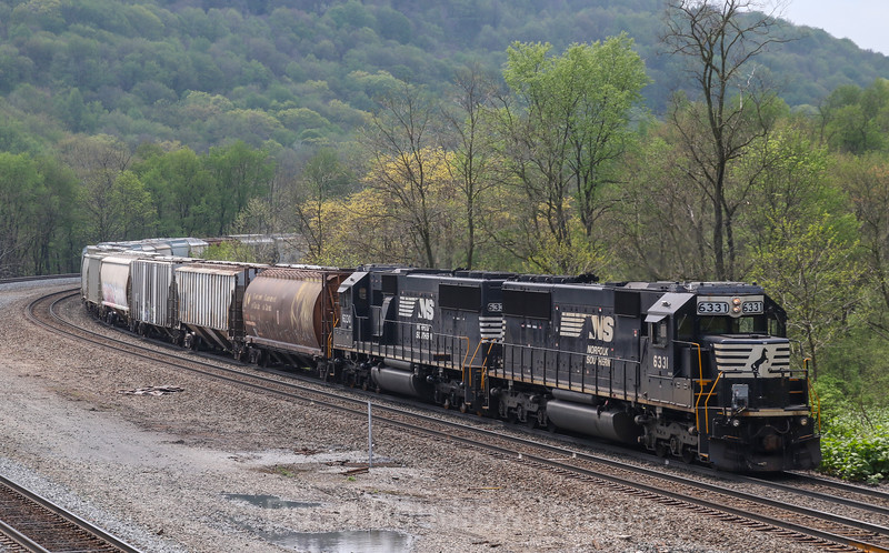 NS Train 35A with helper sets on the front and rear head through the town of South Fork. This town is famous for the 1889 incident in which the South Fork dam failed, flooding nearby Johnstown and killing over 2,000 people, 5-13-18.
