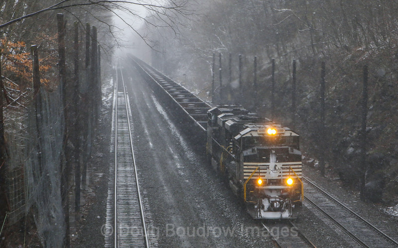 A rare April snowstorm has made the visibility along the mainline in Cassandra nearly zero. NS 1099 leads a set of gondola cars through Cassandra Cut, 4-7-17.