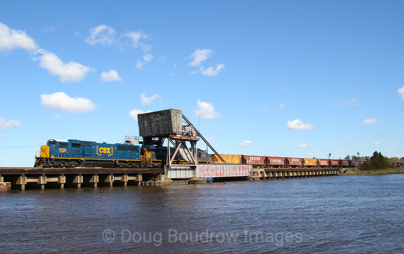 """A loaded ballast train is seen crossing the Ashley River into Charleston, South Carolina bound for Savannah, Georgia on the former Atlantic Coast """"A-Line."""" CSX manifest Q491 is seen passing the North Charleston Amtrak Station headed down the """"A-Line"""" into Bennet Yard, 2-29-20."""