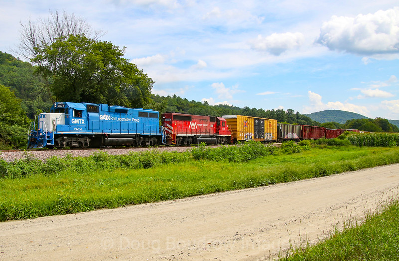 Vermont Rail Systems/Green Mountain Rail Company Train 264 heads North to Rutland passing through farmlands on the outskirts of Chester. The lead unit is a long term lease that VRS has been using on this train.], 8-22-19.