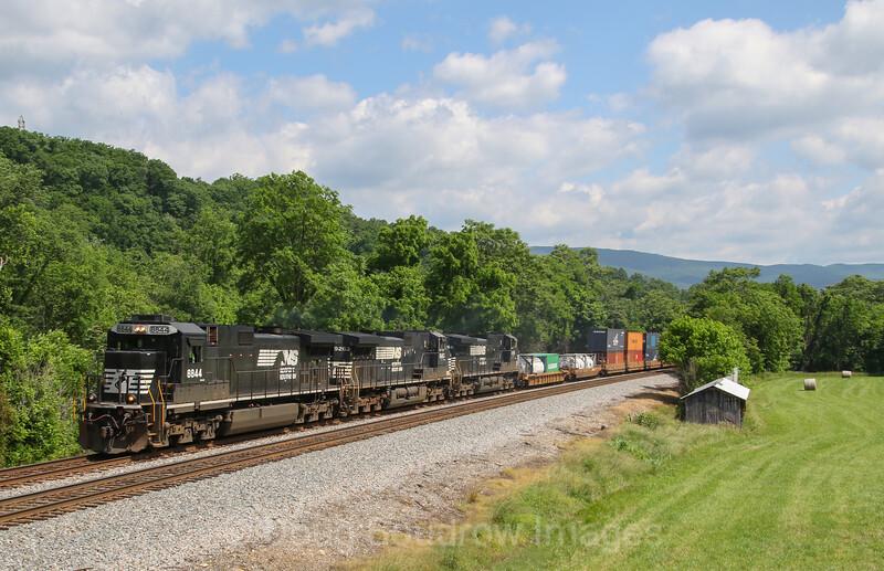 Westbound intermodal train 29G (Norfolk, VA to Detroit, MI) climbs the grade at Gumwood Lane in Wabun next to a freshly hayed farm field, 5-26-17.