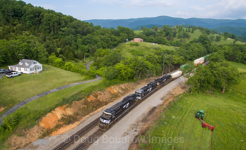 In a typical Southwest, Virginia scene Westbound intermodal train 217 (Charlotte, NC to Chicago, IL) charges up the grade at Shawsville while a farmer totally indifferent to the passing trains cuts his field in his John Deere, 5-27-17.