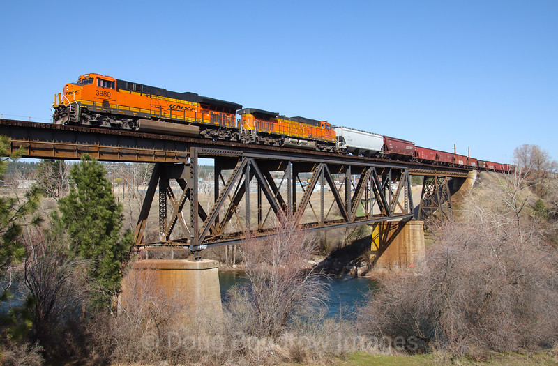 A Westbound BNSF grainer is seen crossing the Spokane River coming into Spokane,  4-6-21.