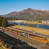 BNSF coal train C-SXMRBG is seen at North Bonneville with the Bonneville Dam in the background at the Western end of the Columbia River Gorge, 7-15-21.