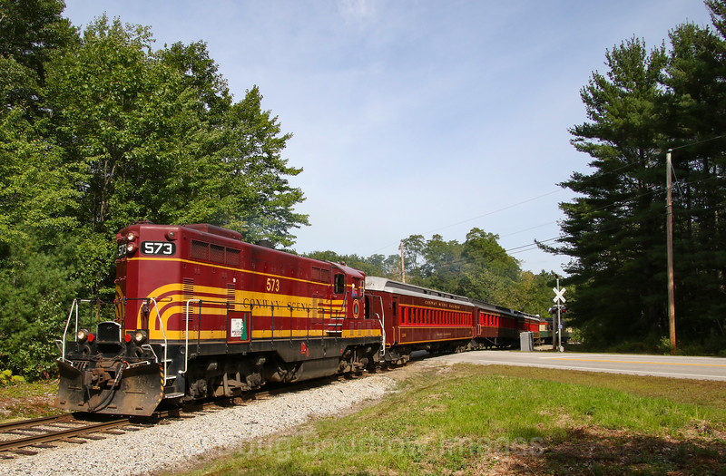 The 10:30 AM Valley Train crosses West Side Road in Conway. The daily morning 55 minute round trip goes from North Conway to Conway on former Boston & Maine trackage. The locomotive 573 is of Maine Central heritage, 9-10-19.