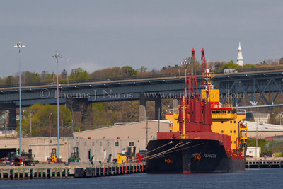 Bow-on view of Persenk The freighter Persenk unloads cargo at the State Pier in New London, CT.  In the background, peeking above the treeline, is the beacon at the US Coast Guard Academy