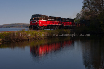 NR-2 and the tiny bridge Much closer now, Providence & Worcester train NR-2 passes by a small tidal pool along the Thames River in Ledyard, CT with the Mohegan-Pequot bridge in the distant background.