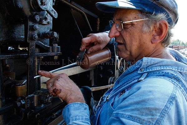 Engineer Fred Jordan tops off the oil on part of 40s running gear - with century-old equipment, lubrication is an ongoing task to keep them running