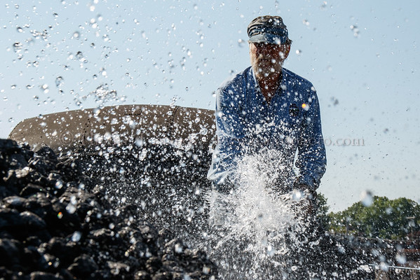 Fireman Bill Frederickson wetting down the freshly loaded coal in the tender