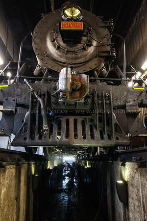 Valley Railroad shop employee Mike power washes the undercarriage of Mikado No. 3025 in the railroad