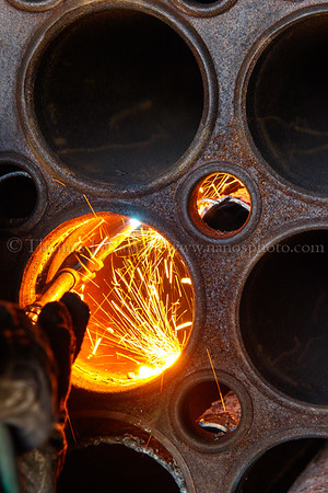 Sparks of molten metal bounce around the inside of a superheater tube
