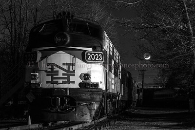 "A former New Haven EMD FL-9 sits quietly on the grounds of the Connecticut Eastern Railroad Museum in Willimantic, CT as the crescent moon sets in the background. This was taken during a test night shoot. It was the first time I had used studio monolights to light a night scene - this was using two lights - one nearly face on, and the other broadside. Traditionally we had used a portable Lumedyne flash, which was used to evenly light the scene. This method enabled the use of shadows to add some depth, and preserve the night ""feel"""