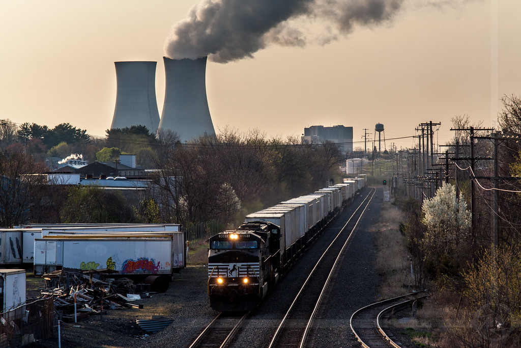 Norfolk Southern train 21E heads west through Pottstown, PA just after sunrise on 4/15/11.  The Limerick nuclear power plant is in the background.