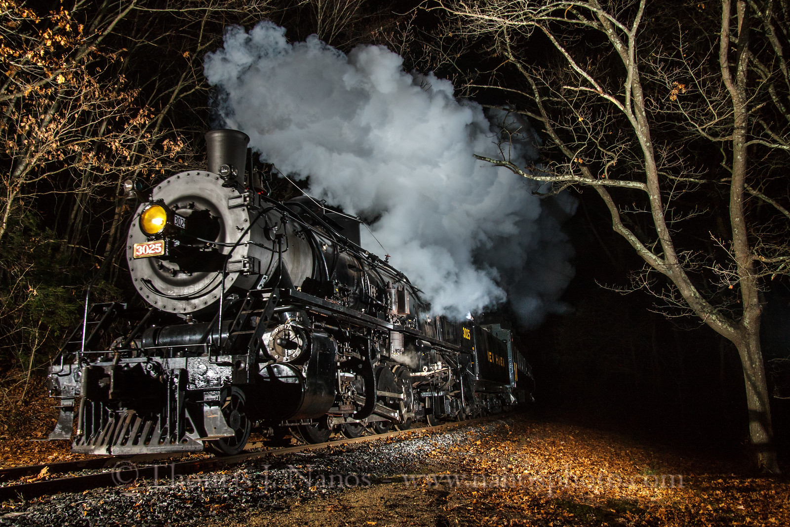 3025, on her first night of revenue service, pulls a trainload of families on the North Pole Express.  Here the train is about to cross over the Old Deep River Road crossing in the Centerbrook section of Essex, CT.