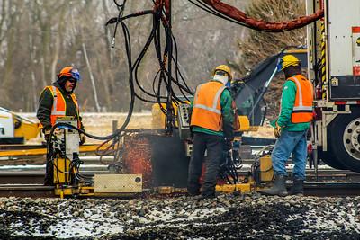 Crews work on welding rail on main track 1.