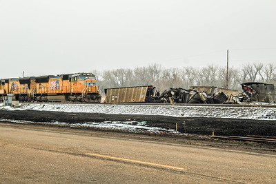 A westbound manifest train passes on main track 2 some of the damaged coal cars that have been collected on the side of the mainline.