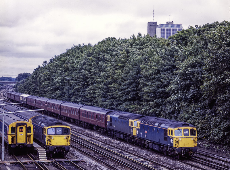 """33114 and 33021 passing Barton Mill Carriage sidings, Basingstoke, with 1Z34, <br /> the 14:49 Woking - Andover, """"Test Valley Steam Ltd"""" on 25th September 1988. <br /> This was a special service organised by Network SouthEast, in connection with <br /> Winchfield 150. It featured a return trip from Andover to Romsey, with Std Tank No. 80080. Scanned Transparency."""