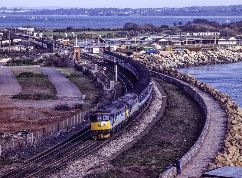 """33050 and 33063 passing Langstone Rock, Dawlish Warren, with 1Z21, <br /> the 07:15 Basingstoke - Falmouth Docks, on 21st March 1992. <br /> This was the """"Cornish Construction Crompton"""" organised by Merlin Railtours. <br /> Scanned Transparency."""