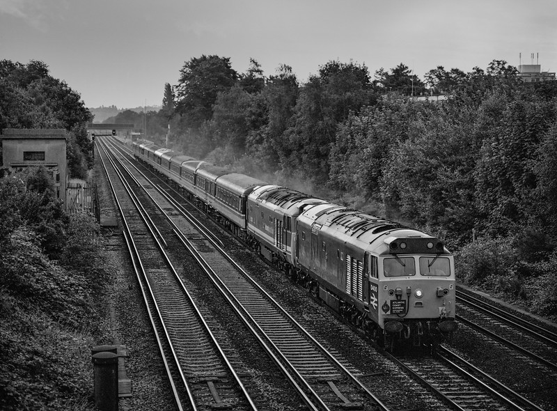 """50050 (D400) and 50033 at Sheerwater Road, West Byfleet with 1Z41, <br /> the 08:35 Waterloo - Exeter St Davids, on 18th July 1993. <br /> This was the """"Atlantic Coast Express"""" which would also visit Barnstaple and Exmouth, organised by Hertfordshire Railtours. Scanned Negative."""