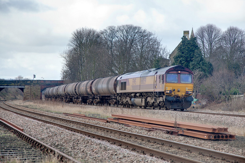 66059  passing Forge Lane, Horbury Junction with a 6E32 Preston to Lindsey empty bitumen tanks on February 19th 2010.