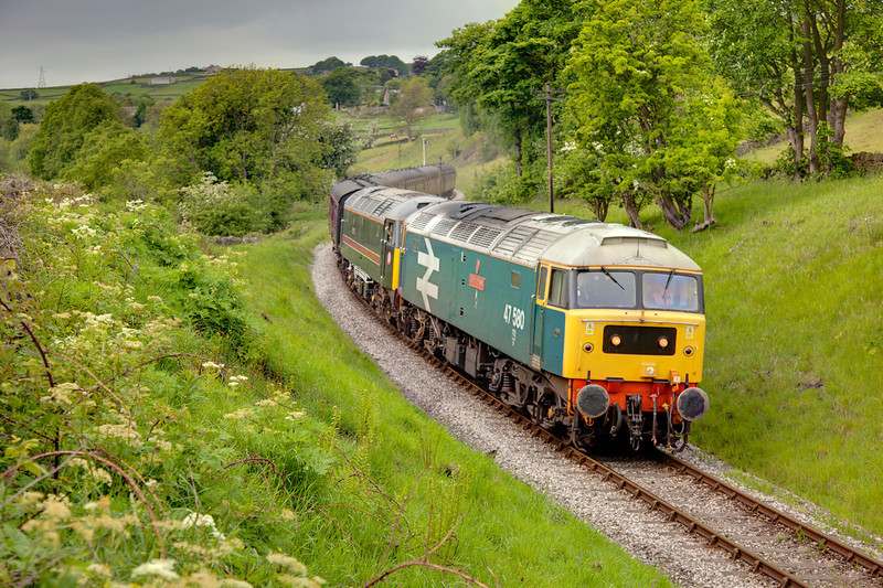 Under an ominous sky, 47580 pilots 47715 downgrade between Oakworth and Damems with the 12:05 Oxenhope to Keighley on May 20th 2011
