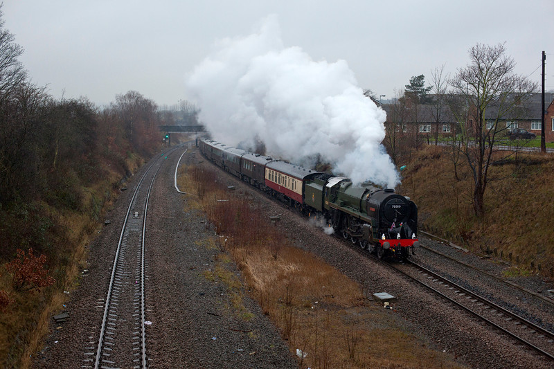 """70000 Britannia slows for a signal check at Horbury Junction while in Charge of an 08:00 Preston to Wakefield Royal Train conveying Prince Charles to a re-dedication of 70000 Britannia at Wakefield Kirkgate station. The train then ran empty to York where the kettle was removed and """"skip"""" six, which was bolted on the rear returned the rolling posh hotel to its Wolverton base. Crap full rain weather meant I had to shoot a 2000 ISO!"""