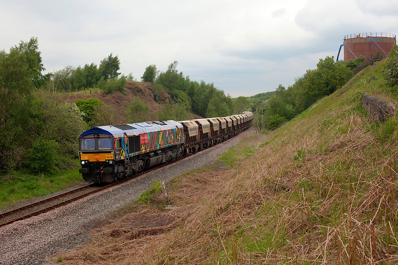 As workers repair a Gas Storage Tank at Royston Coking Plant 66718 rolls through the adjacent cutting with the 6E84 08:20 Middleton Towers to Monk Bretton on 15th May 2014.
