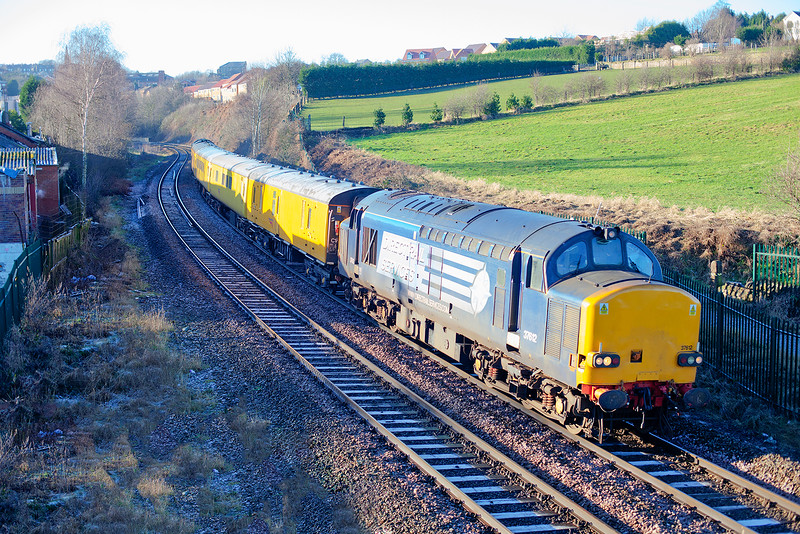 With the frost still clinging to the shadows, 37612 leads 37259 past the site of the former Gas Works Crossing, Morley with a late running 1Q26 08:00 Wigan LIP to Derby RTC on 4th January 2014.<br /> <br /> The foot crossing was removed and replaced by a footbridge after a fatality involving children playing on the line