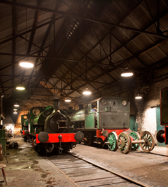 General shed view from halfway in with the orange glow of the forge visible in the background