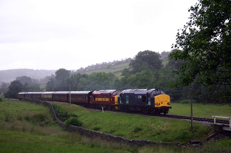 37259 leads 37670 through Haworth Meadow in a torrential Downpour with the 15:25 Keighley to Oxenhope on June 20th 2004