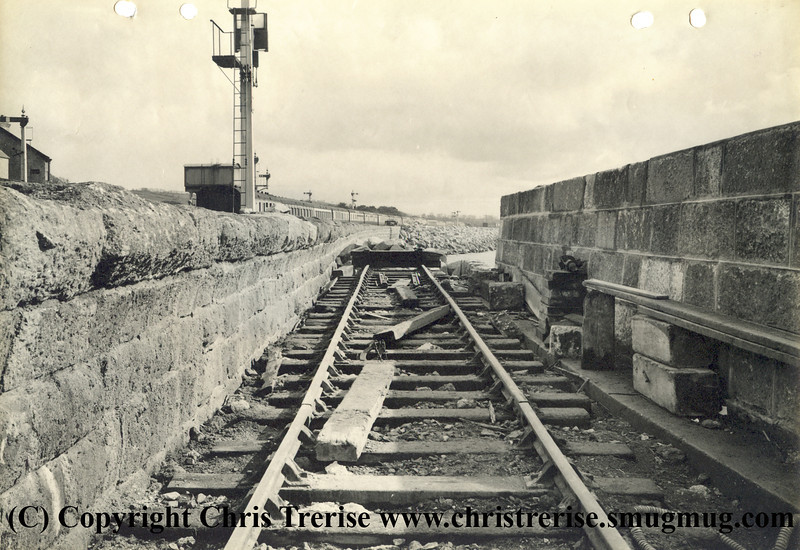 "Penzance station showing the siding used to tip rubble into the sea during rebuilding work to extend the number of platforms. The photograph is stamped on the rear ""GWR Chief Engineer's Office Paddington Photographic Department"".<br /> 16th April 1940"