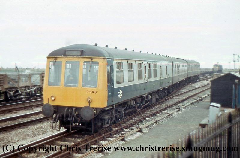 Class 119 3 Car DMU Set number P596 arrives at Dawlish Warren.  An unidentified Class 47 can be seen in the background on an empty clay working.<br /> 8th August 1980