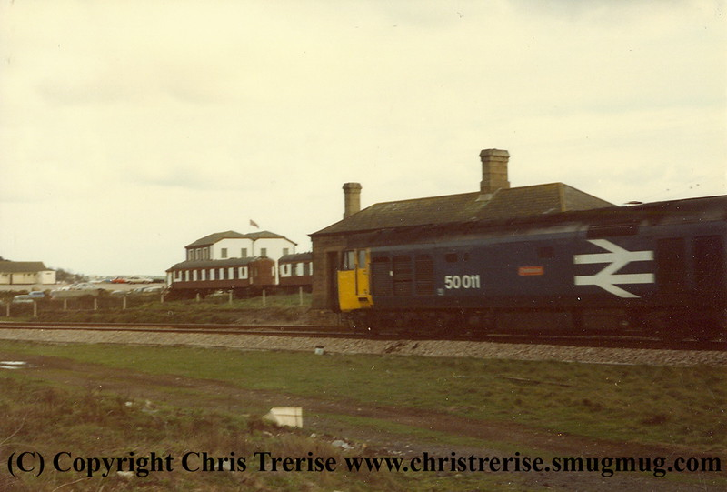 "Class 50 Diesel Locomotive number 50 011 named ""Centurion"" passes the closed station at Marazion with the 1410 Penzance to Plymouth in 1984.  The pullman coaches clearly visible marooned on an old siding behind."
