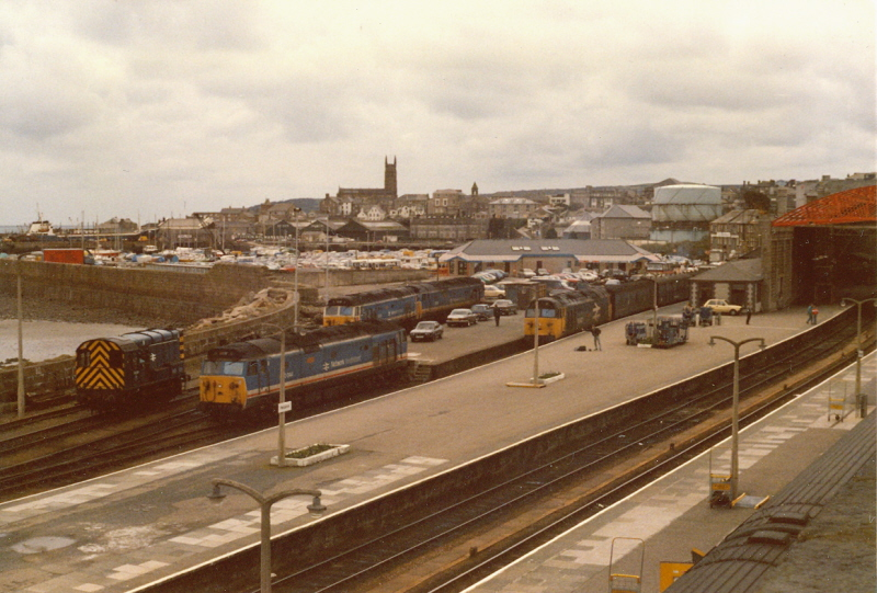"The view over the wall at Penzance.  On the left is Class 08 Diesel Shunter number 08 801.  Alongside is Class 50 Diesel Locomotive number 50 044 named ""Exeter"" and behind this are Class 50s 50 034 named ""Furious"" and 50 027 named ""Lion"".  Finally 50 047 named ""Swiftsure"" is at the head of the parcels working.<br /> 2nd April 1988"