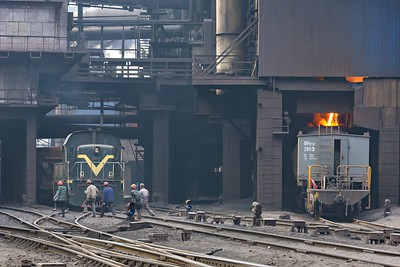 Workers walk past the Blast Furnaces