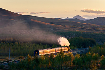 QJ #6911 heads into the sunset with a passenger service
