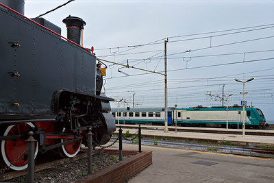 Plinthed 0-6-0T rack loco looks on at Trenitalia 464-014 at Catania Centrale