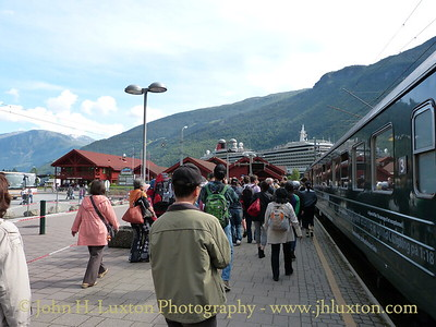 Flåmsbana photographed on Monday August 06, 2012. Passengers disembarking at Flåm. The Carnival Corporation cruise ship QUEEN ELIZABETH can just be seen at the cruise terminal on the quayside.
