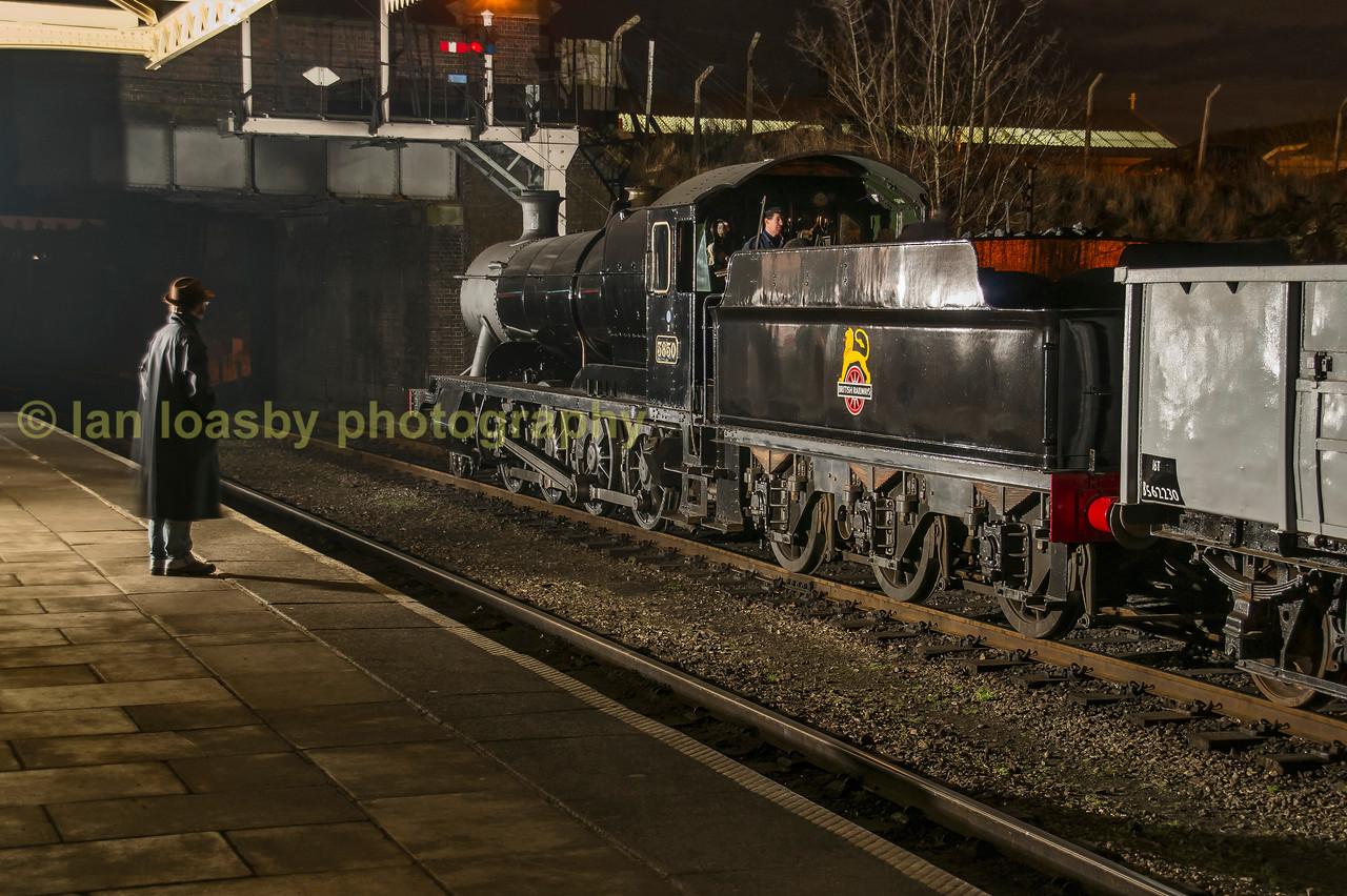 Late night passenger looks at a coal train whilst awaiting his train, Loughborough central