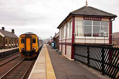 Northern Rail sprinter 156469 and 153358 make their station stop with 2H10 0849 Leeds to Carlisle train. The former Midland Railway signal box is slowly sinking into the ground outside the fence, hence the odd angle of it.